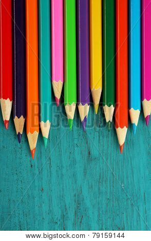 Colorful pencils on color wooden background