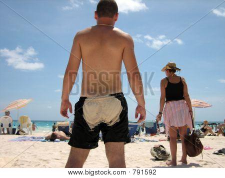 a guy on the beach with sand on bum
