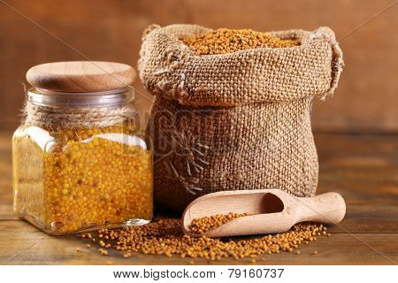 Mustard seeds in bag and Dijon mustard in glass jar on wooden background