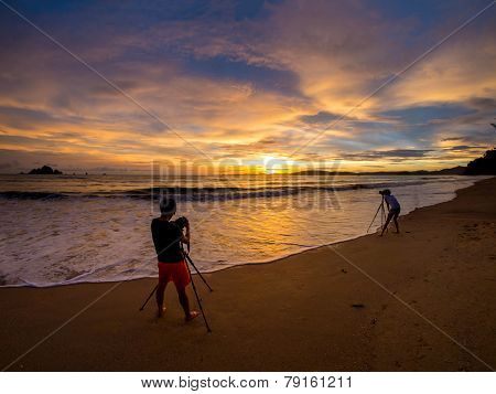 People taking pictures of the Sunset on the beach of Ao Nang in Krabi Thailand