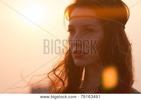 Portrait of a hippie woman with headband looking far away at sunset with windy hair