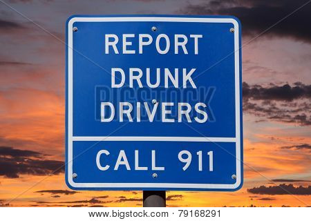 Report drunk drivers highway sign with sunset sky.