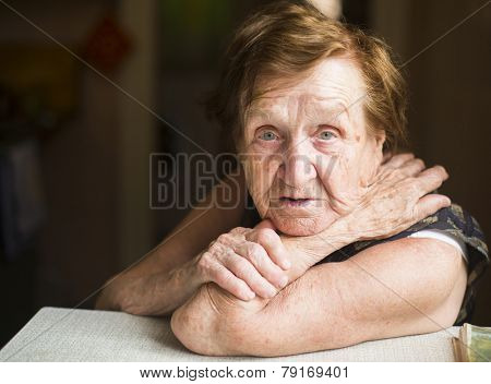 Poor old woman in her home, looking into the camera.