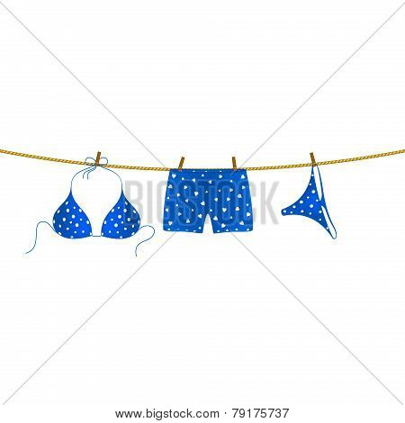 Blue bikini suit with white dots and boxer shorts with white hearts hanging on rope