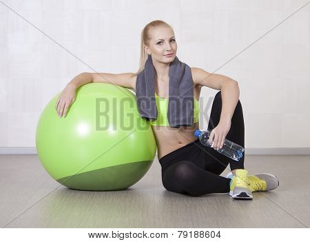 Woman in a gym resting after training with fitness ball