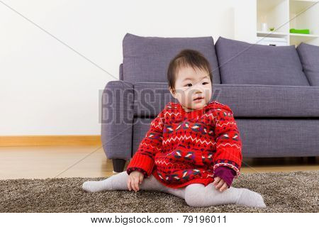 Baby girl seating on carpet at home
