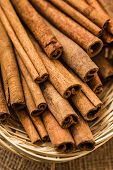 stock photo of cinnamon sticks  - Cinnamon sticks in straw basket on a linen napkin - JPG