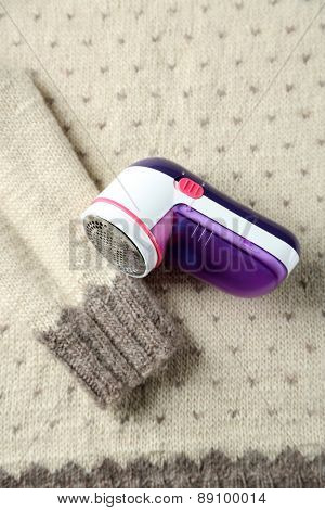 Wool shaver on wool sweater background