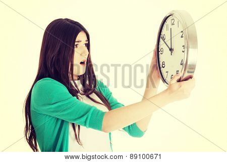 Surprised woman holding a big clock