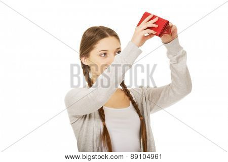 Unhappy teen woman with empty purse.