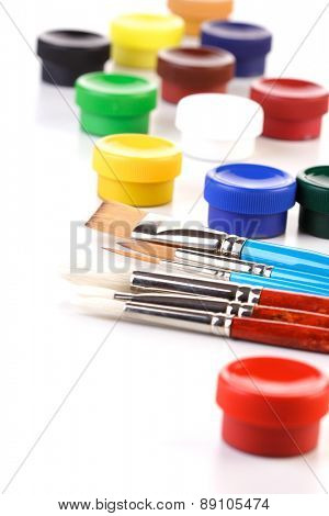 Paint boxes and brushes on white background