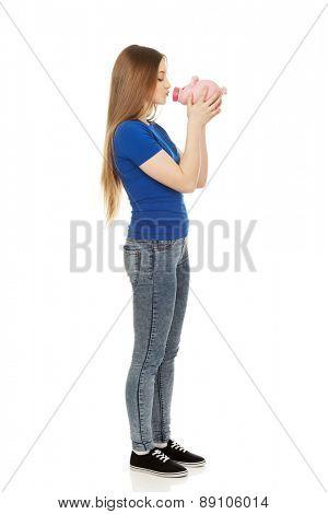 Happy teenage woman kissing piggybank.