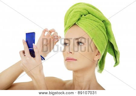 Beautiful caucasian woman plucking her eyebrow.