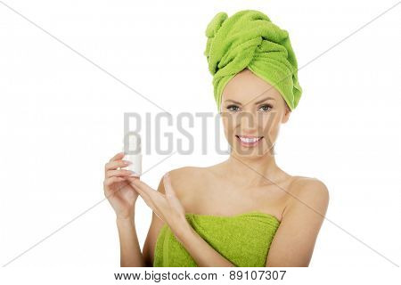 Young woman wrapped in towel holding deodorant.