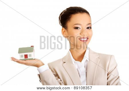 African businesswoman holding small house on palm.