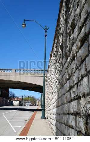 Lamppost Next To a High Wall