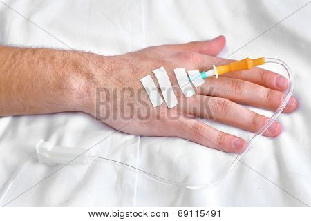 Man hand with dropper needle on bed close-up