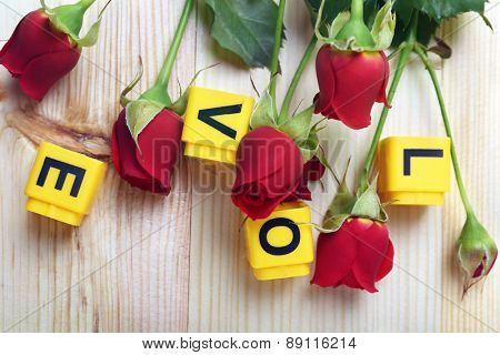 Beautiful roses with word LOVE on wooden background