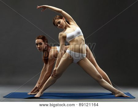 Harmonous young women practicing yoga in pair