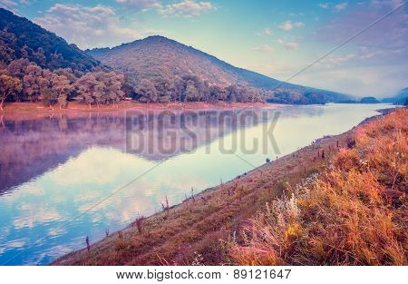 Fantastic foggy river with fresh grass in the sunlight. Dramatic unusual scene. Warm sundown on Dnister. Ukraine, Europe. Beauty world. Retro and vintage style, soft filter. Instagram toning effect.