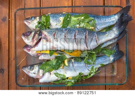 raw prepared organic sea bass stuffed with herbs and lemon