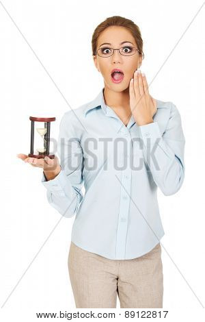 Beautiful shocked businesswoman holding a sandglass.