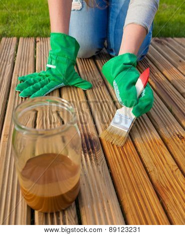 Applying protective varnish on a patio wooden floor, house improvement concept