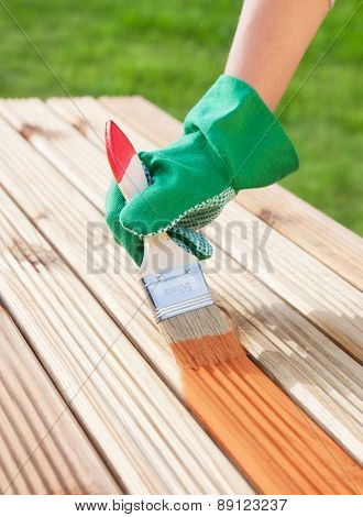 Applying protective varnish on a patio wooden floor, diy maintenance concept