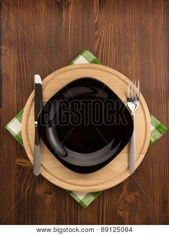 kitchen utensils at cloth napkin on wooden background