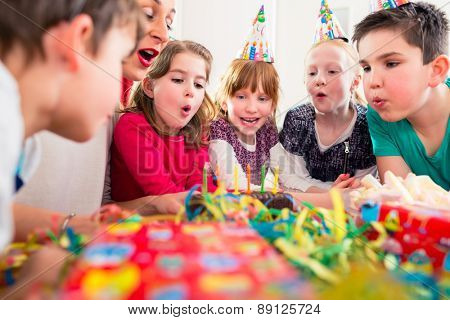 Child on birthday party blowing candles on cake being helped by friends and the mother
