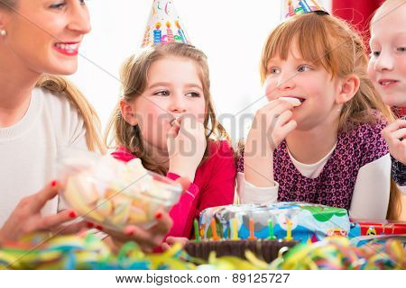 Children on birthday party nibbling candies wearing party hats