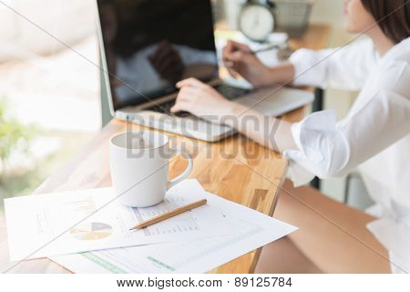 Beautiful Business Woman Using A Laptop Computer And Writing On Business Document