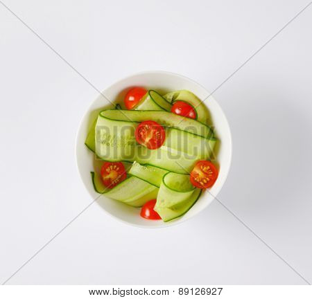 overhead view of bowl with cherry tomatoes and cucumbers