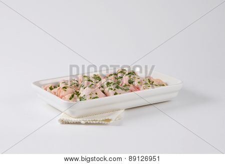 chicken legs with herb marinade, ready in the porcelain tray