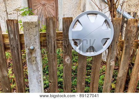 old fence and aluminum rim, the symbol of patchwork, decay, temporary