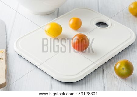 mini tomato on white chopping board