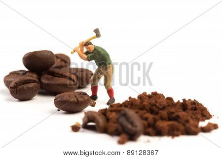 Miniature worker with axe working on a coffee bean