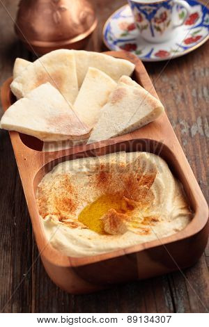 Hummus with sliced pita bread on a rustic table