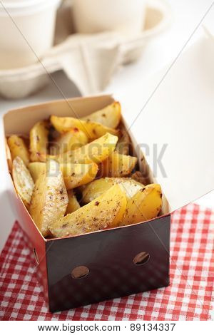 Takeout roasted potato in a paper box