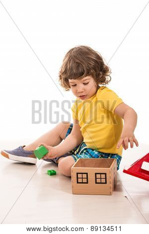 Toddler Boy Playing With Wood House Toy