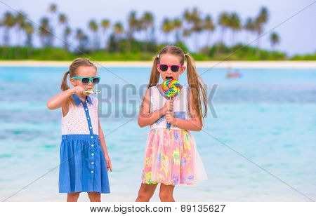 Adorable little girls with lollipop on tropical beach