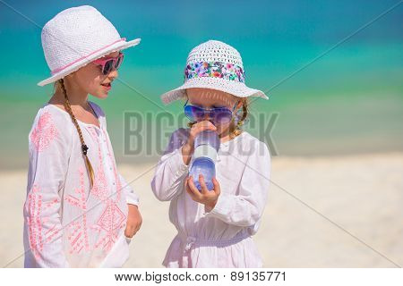 Little girl drinking mineral bottle of water at hot summer day on beach