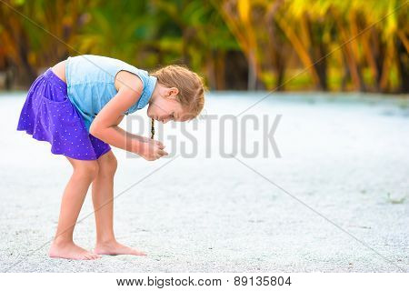 Little girl collecting seashells on white sand beach