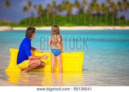 Little girl and young father with air mattress on summer vacation