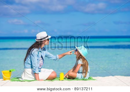 Mother applying sun protection cream to her daughter at tropical beach