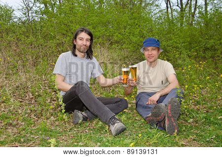 Two happy men talking and drinking beer