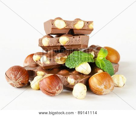 bar of chocolate with hazelnuts and mint leaves on a white background