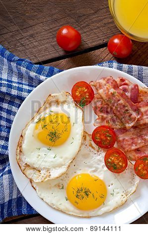 English breakfast - egg, bacon and vegetables in a rustic style on wooden background.