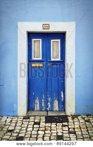 Blue wooden door in the facade of a typical Portuguese house