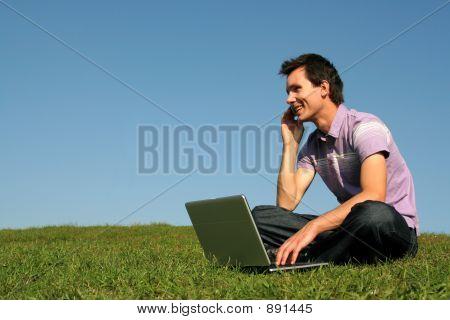 Hombre con ayuda de un ordenador portátil al aire libre